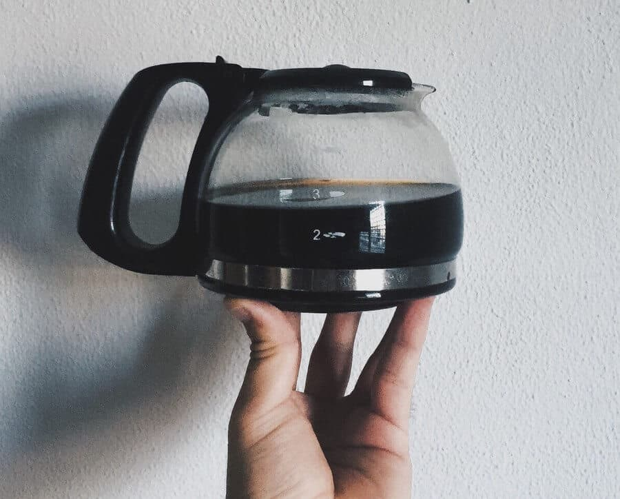 A hand holding up a small pot of coffee.