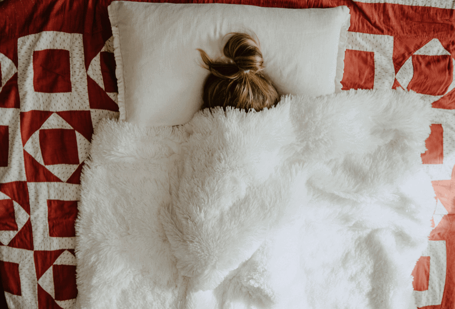 Girl under white fur textile covers.