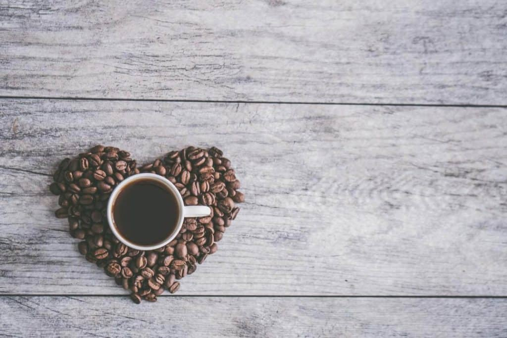 A picture of a cup of coffee surrounded with coffee beans