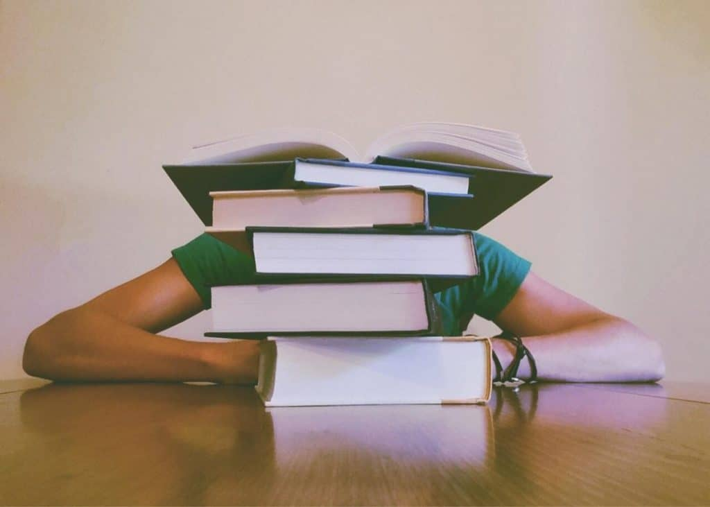 Stack of books with person slumped over.