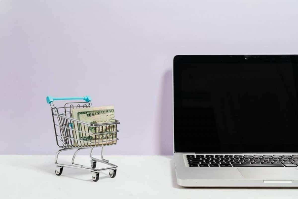 Tiny cart full of cash beside a laptop