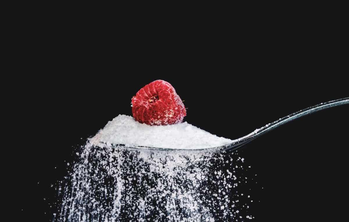 Teaspoon of sugar with a raspberry on top