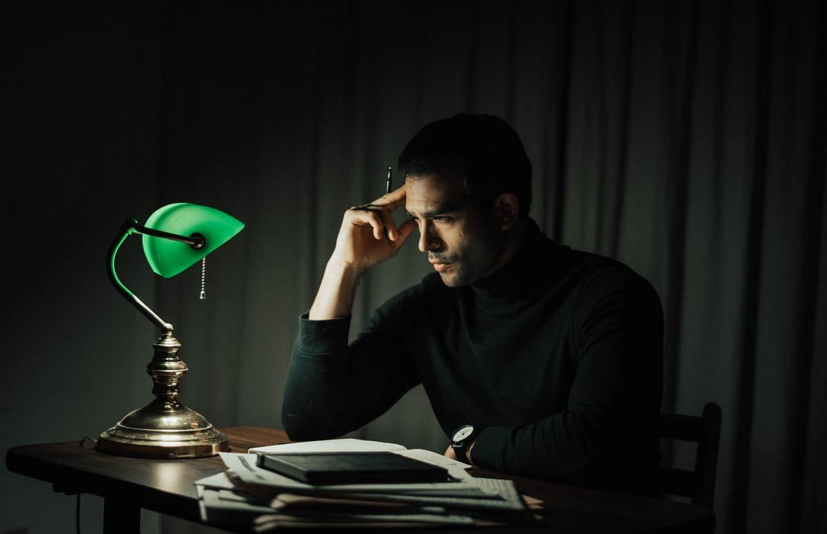 Wistful man with documents at table in dark room