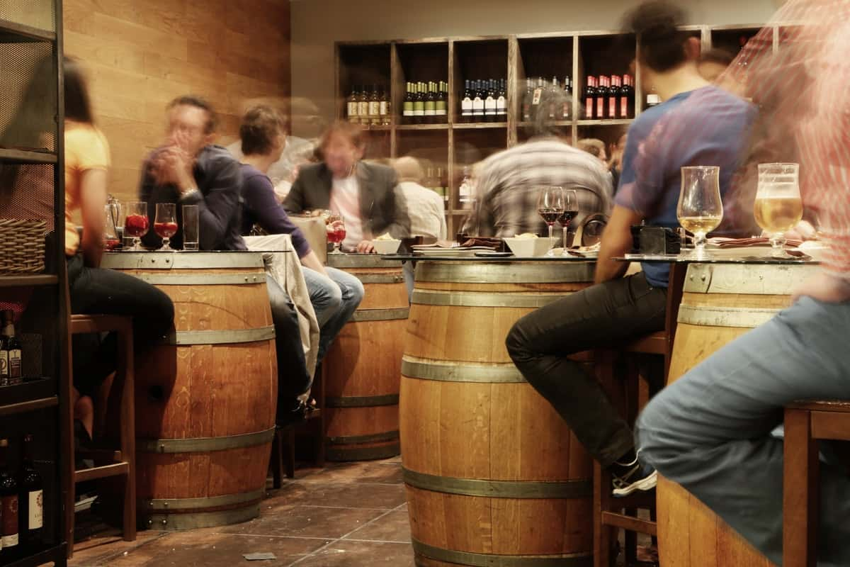 People drinking while sitting on barrel chairs