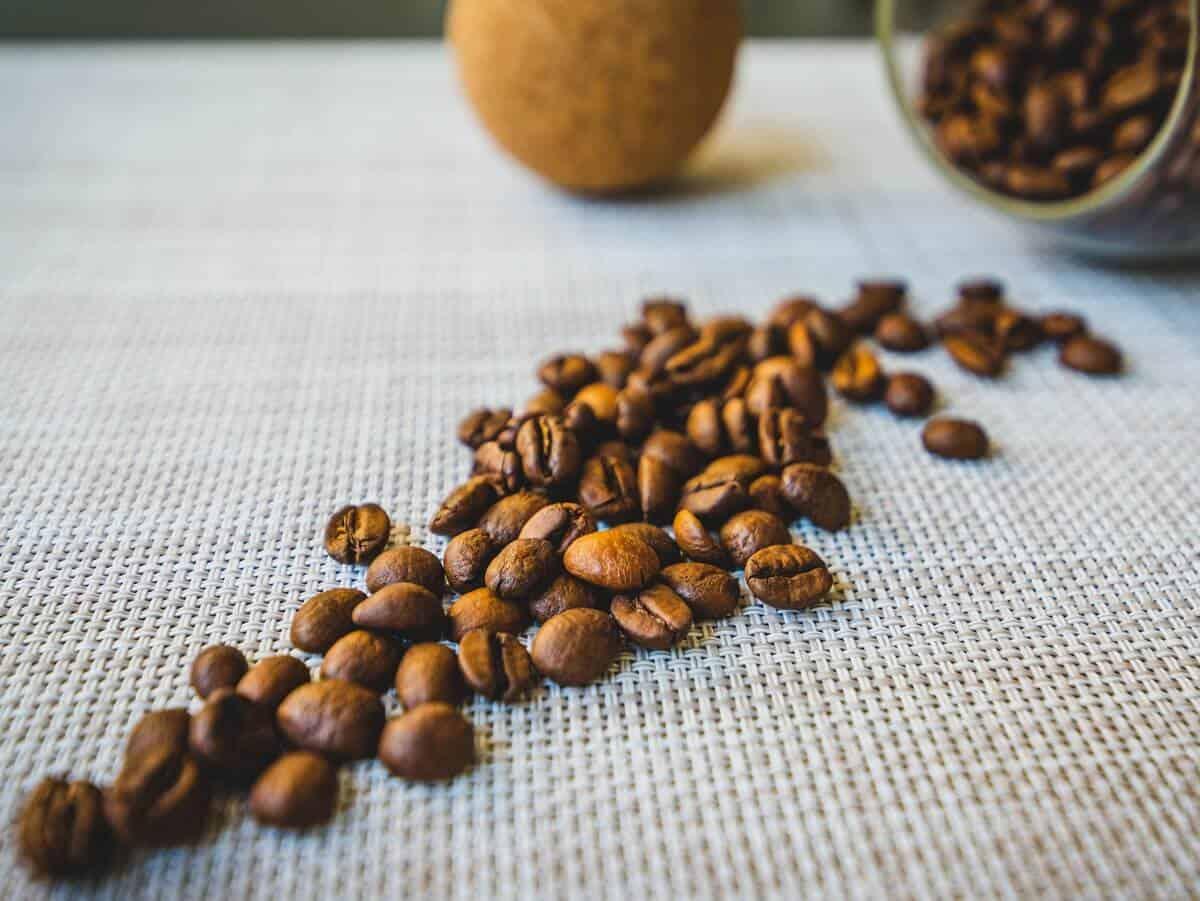 Caffeine beans on  white sheet table